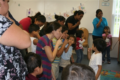Moms and kids sing educational song at Grace Place