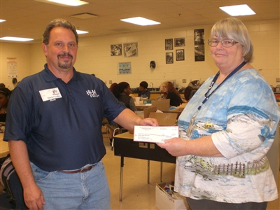 HUM's Mark Geallis accepts check from Marcia Bobbitt