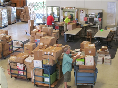 Workers help get packages ready to ship at Agape Flights