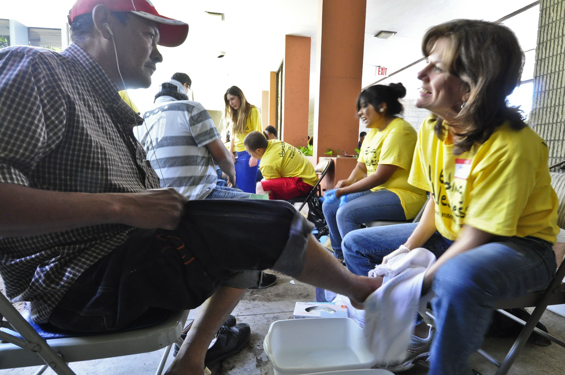 Dr. Cynthia Weems, First Miami pastor, right, washes the feet of a homeless man