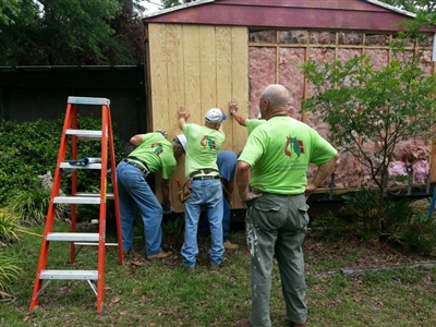 United Methodist volunteers replace siding on flood-damaged home