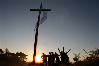 Silhouette of FGCU and CCW mission team against African Sunset with cross