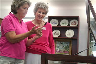 Anita Campbell, left, and Nell Thrift look at some hymn books at the Archives Center