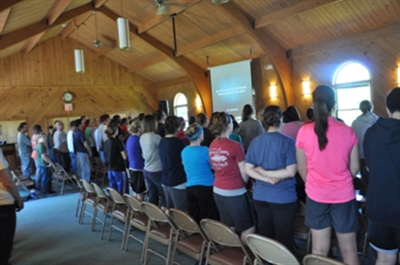 Youth and residents (backs turned) pray together at His Mansion Ministries