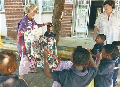 Missionary cuts up with young African children receiving new clothes