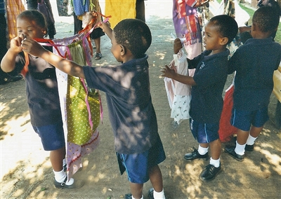 A young African boy holds a new dress up for a classmate
