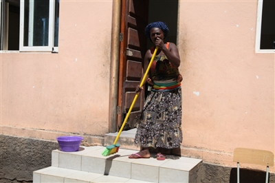 A woman in Quessua sweeps her front steps with a child on her back