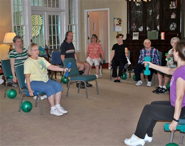 Seated exercise participants use weights and squeeze balls