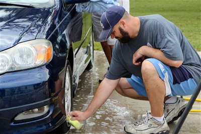 Matthew Rawls scrubs a hubcap in a free community carwash at Springhead UMC