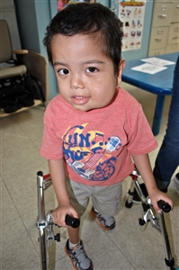 Preschool boy using a walker and smiling at camera