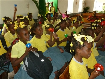 Sunday school children in yellow shirts raising hands, looking animated