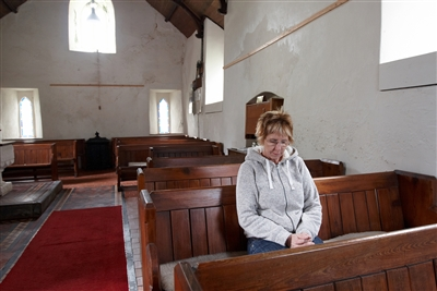 A casually dressed woman prays alone surrounded by empty pews
