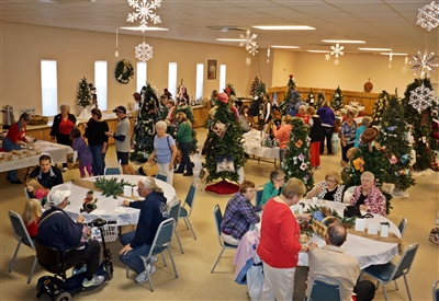 Shoppers mill about through decorated trees and display tables