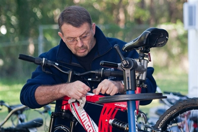 Trevor Charlton of Toymakers at East Lake UMC works on a bicycle