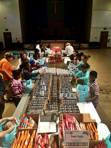 Children and adults packing food in assembly lines