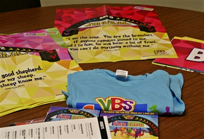 Shirts, pamphlets and other VBS materials with scriptures on display table