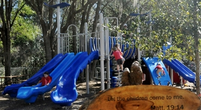 Children on a slide and play apparatus with Jesus quote on a sign in front