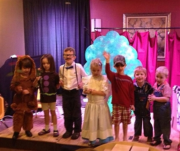 Children in costume take a bow on stage after a performance