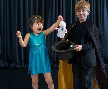 A girl pulls a rabbit from a hat held by a boy in magician's costume