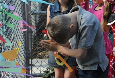 A boy prays during the opening ceremony for accessible playground at Trinity UMC
