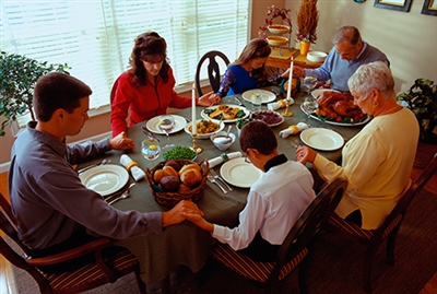 Family praying at holiday meal