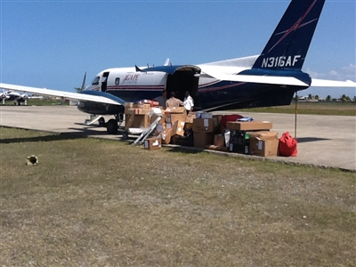"Agape Flights ""Bandit"" plane being unloaded by missionaries"