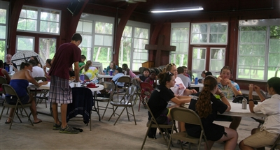 Campers dine at the Red Pavilion at Riverside Retreat