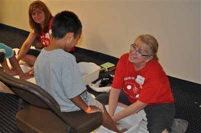 Boy gets his feet washed before receiving free shoes at Grace Church, 2011