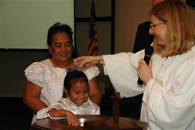 Rev. Nancy Mayeux baptizes a girl at Micronesian Mission