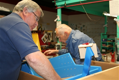 Volunteer Ted Emack packs part of a PET unit in box for shipping