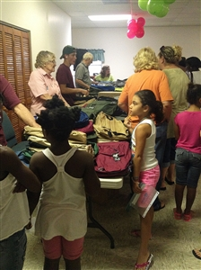 Children report to the table where Trinity UMC volunteers hand out backpacks