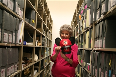 Nell Thrift stands in archives storage shelves holding Disney hat of late Bishop Hunt