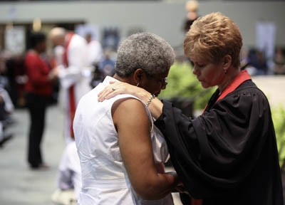 Rev. Catherine Fluck Price, right, prays with a lay member at Annual Conference 2010