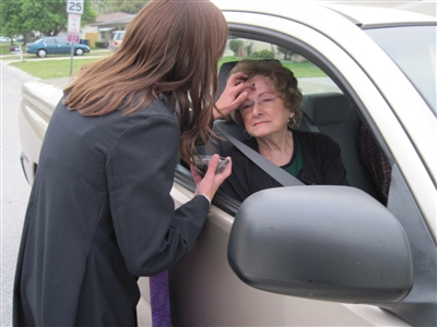 Rev. Emily Oliver administers ashes to Judi McKeel sitting in a car