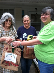 Patricia Walton and Carolyn Hogsett receive food from Rev. Priscilla Scherrah