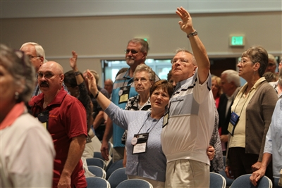 Laity crowd with upraised hands