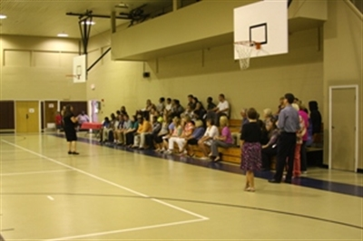 Students and teachers in a gym assembly