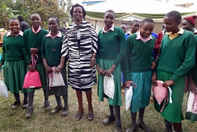 Lucy Mbae poses with girls in Kenay who received comfort kits from Florida