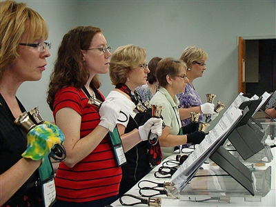 A row of women ringing handbells