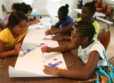 Youth girls check out each other's work at the crafts table