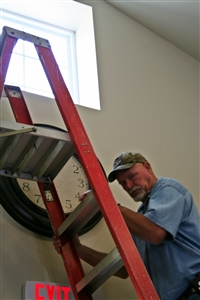 Mike Moore, operations director, hangs a clock on the wall of a group home