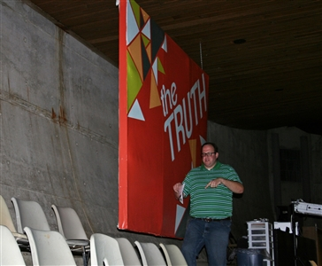 Rev. Mike Toluba in front of a banner that hides a large crack in the chapel wall