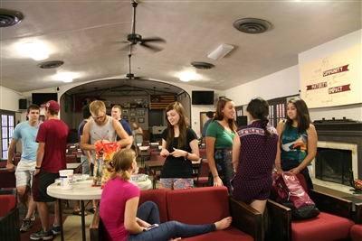Students talk and relax on sofas and chairs in the FSU Wesley fellowship hall