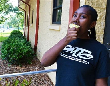 A teenage girl eats an apple outside a Summer BreakSpot site in Tallahassee