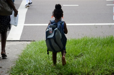 Small child with large backpack leaves Riverside Park UMC's back-to-school event