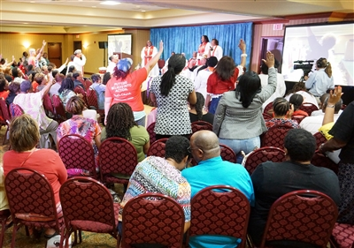 Wide shot of opening worship has attendees with arms raised