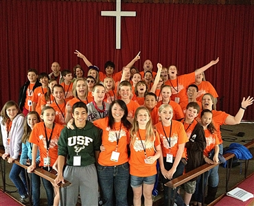 Group shot of a confirmation class under the cross in worship space