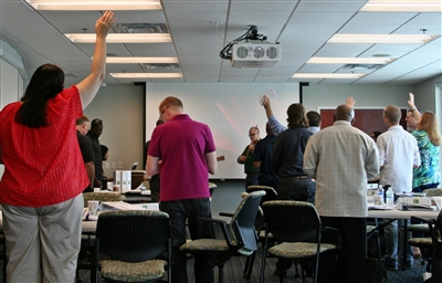 Participants raise their hands in praise at the opening worship service