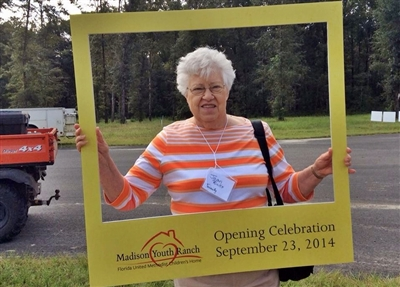 Woman posing with picture frame labeled Madison Youth Ranch opening