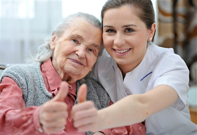 Senior woman and younger woman close together giving thumbs-up sign
